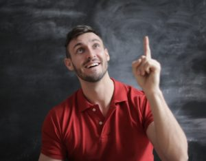 Man in a red polo shirt in front of a blackboard holding up a finger as though he's had a good idea