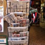 A full newspaper and magazine stand outside an open shop
