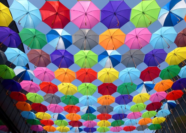 Multi-coloured open umbrellas strung together in the air between two buildings under a blue sky