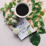 A cup of black coffee on a wooden board with macaroons and some sprigs of greenery with a note displaying the message enjoy the little things
