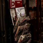A metal newspaper stand outside a shop filled with newspapers and the words International Press at the top
