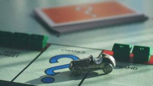Help your team thrive, car playing piece landing on chance on a Monopoly game board