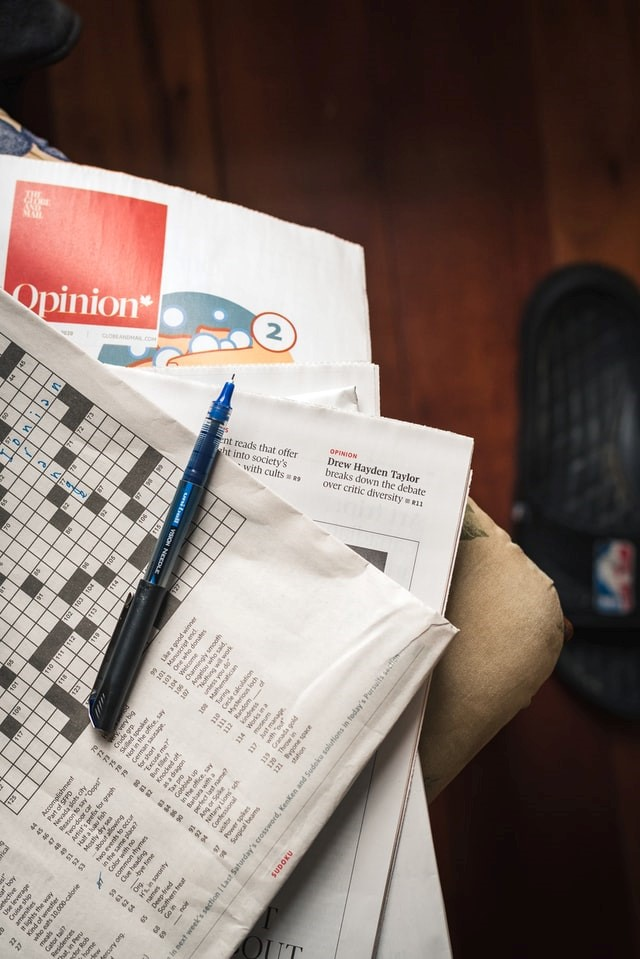 A small fan of newspapers with the word opinion showing and an unfinished crossword with a pen lying open on top of the pile