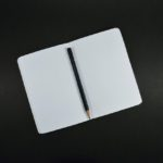A notebook opened on two blank white pages with a pencil lying on the centre spine