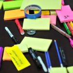An assortment of sticky notes and pens mixed up on a table-top for health in the workplace resources in Spring newsletter