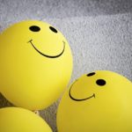 Two yellow smiley emoji against a grey textile backdrop