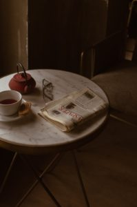 Chair and marble topped table with a folded newspaper, pair of folded glasses, a red teapot and a white half-filled cup and saucer with a biscuit perched on it