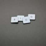 Four tiles each with a letter spelling out the word BLOG set overlapping on a dark grey background