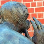 The Listening bronze sculptor looked at from behind. A head and shoulders with a hand up, cupped beside the right hand ear to signal listening - for the Listening Skills tip in our Spring newsletter