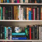 Assorted labelled books on white bookshelves