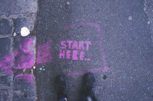 """Tarmac and cobbled surface with a pair of feet and a pink """"start here"""" message written in a square box in front of them."""