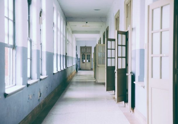 School corridor with windows on one side and classroom doors on other.