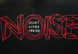 Black background with the word 'noise' in red and the words 'quiet lives inside' in white placed within the 'o' of noise.