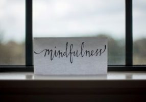A white piece of paper with the word mindfulness written on it propped on a windowsill with blurred view in the background