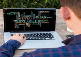 Man in checked shirt looking at laptop on a wooden table outside. Laptop has a mental health word map on the screen.
