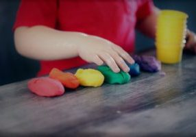 Soft skills training courses - photo of a person standing at a table with 6 different coloured pieces of modelling dough in front of them
