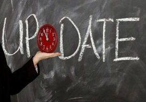 The word 'update' in white chalk on a blackboard with a red clock held on the open hand of the arm of a suited person.