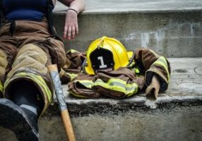A yellow hard hat resting on a brown and yellow firefighter's suit beside a firefighter sitting taking a break